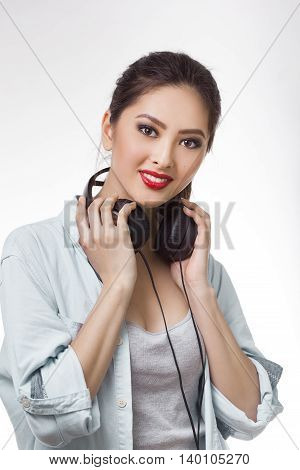 Music. Woman holding big earphones headphones listening to music on mp3 player. Playful happy smiling young mixed race Asian Caucasian woman isolated on white background.