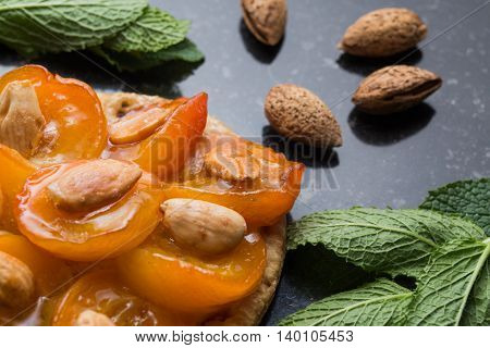 Tart With Apricot. Traditional French Pie With Fruits On Dark Marble Background. Decorated Almonds A