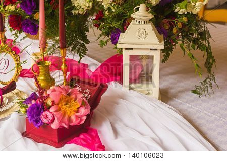 Wedding set on the table: box for rings decorated flowers and metal lantern