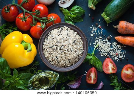 Ingredients for cooking - rice vegetables and herbs. Top view with copyspace. Organic food background.
