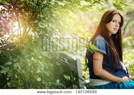 Young beautiful woman expecting baby. Calm mood summer outdoor looking in camera. Selective focus. Space for text.