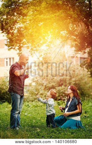Full-body Of Happy Family In City Park At The Sunset