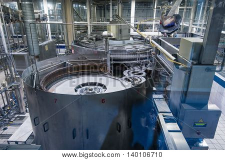 Equipment that pours beer into bottle at big brewery plant