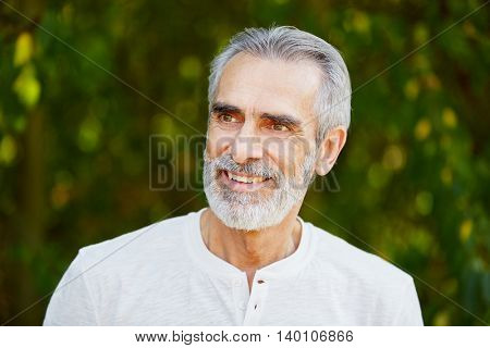 Senior retired man smiling with joy in summer in the nature