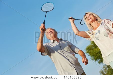 Happy senior couple playing badminton togheter as a team in summer