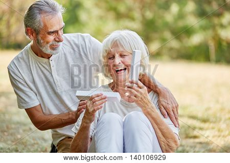 Old man surprises smiling woman with present in the garden in summer