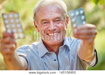 Senior man holds medicament with joy in the nature