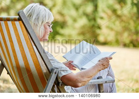 Old pensioner reading a book in summer in the nature