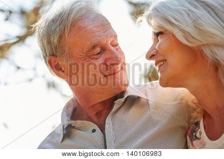 Senior couple in love looks at each others eyes in summer