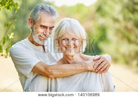 Happy seniors in love hugging in summer in the nature