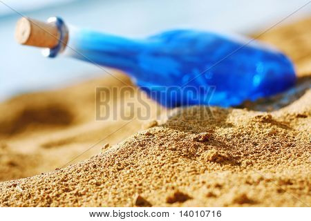 Blue bottle with cork on sea side. Focus on sand