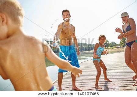 Happy family spray each other with water at a lake and have fun