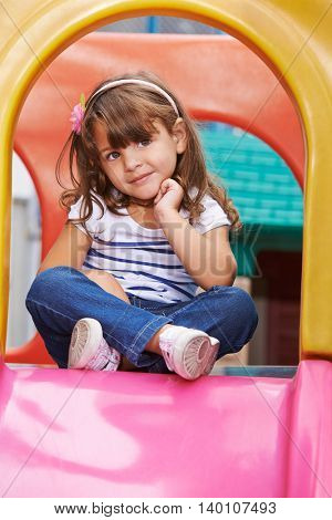 Girl sitting in tailor seat on a slide in a playground
