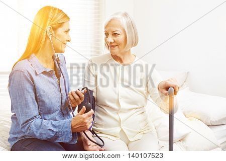 Woman doing blood pressure monitoring in nursing home for senior woman