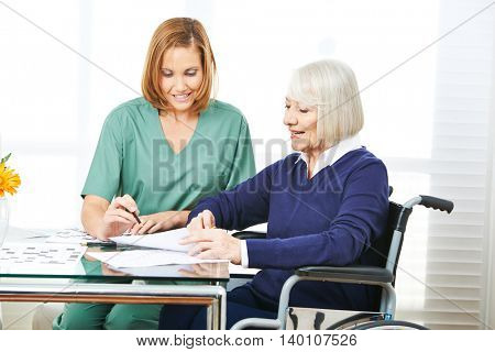 Caregiver helping senior woman in wheelchair filling out contracts