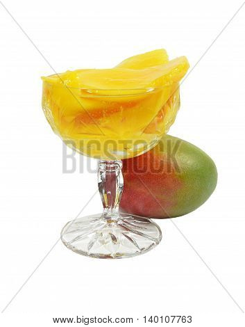 Stewed mangoes in crystal tall glass. Nearby lies whole uncut ripe mango. Isolated on white background