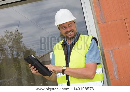 Happy Entrepreneur On Construction Site Using Electronic Tablet