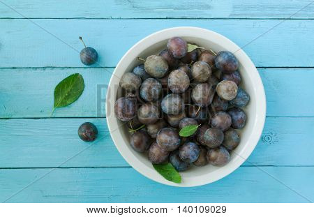 Fresh ripe plums in bowl on blue wood background