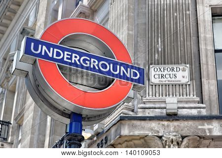 LONDON - JULY 1 2014: London underground sign at Oxford Circus Station with the focus on the Underground sign.