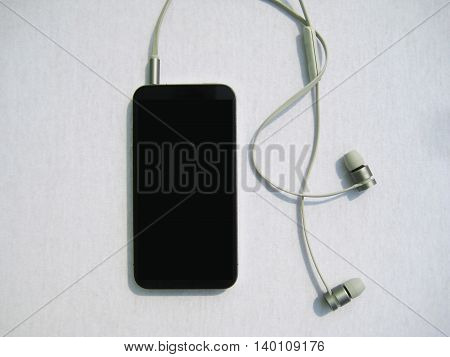 Black mobile phone with grey headphones for music listening