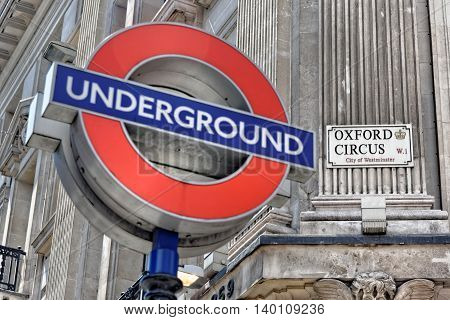 LONDON - JULY 1 2014: London underground sign at Oxford Circus Station with the focus on the Oxford Circus sign.