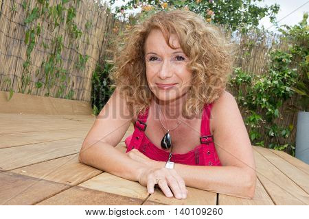 Pretty Blond Middle Aged Woman Laying On Pool Deck