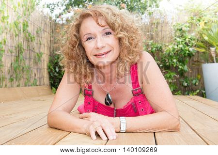 Smiling Blond Middle Aged Woman Laying On Pool Deck