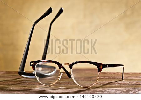 two eyeglasses on the table with brown background