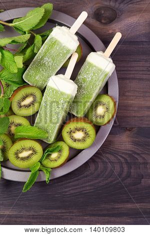 Homemade frosty kiwi popsicles on a plate with mint and kiwi slices on a dark wooden background. Top view with copyspace