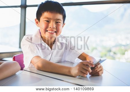 Schoolkid using mobile phone in classroom at school
