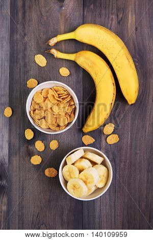 Healthy breakfast - cereal and a banana on a dark wooden background