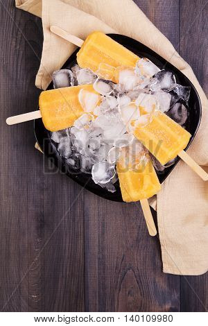 Homemade orange popsicles on a plate with ice on a dark wooden background. Top view with copyspace