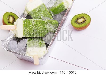 Frosty popsicles of kiwi in a box on a white wooden table