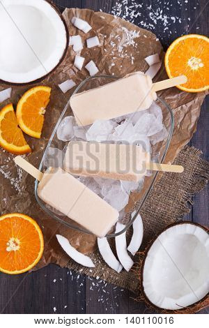 Homemade orange and coconut popsicles on a plate with ice on a dark wooden background