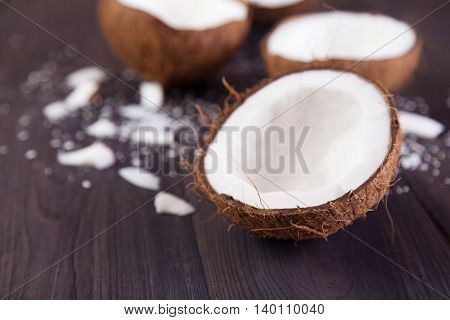 Coconut halves with shell on a dark background