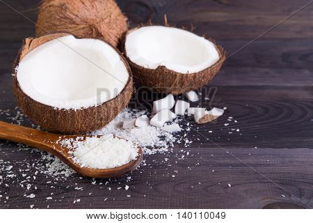 Coconut halves with shell and shavings on a dark background