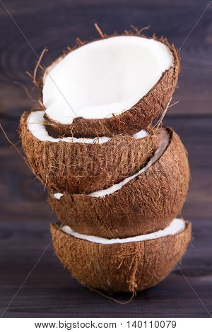 Coconut halves with shell on a dark wooden table
