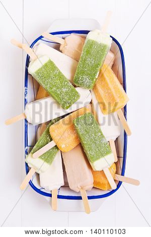 Homemade orange kiwi coconut and peach popsicles in a plate on a white wooden background
