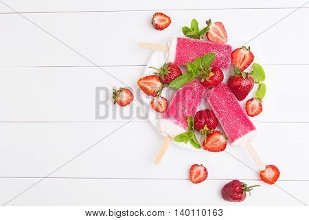 Homemade strawberry popsicles on a plate with mint on a white wooden background