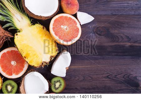 Tropical fruits - pineapple peach kiwi grapefruit and coconut on a dark wooden background. Top view with copyspace
