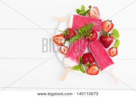 Frosty strawberry popsicles on a plate with mint on a white wooden background. Top view with copyspace
