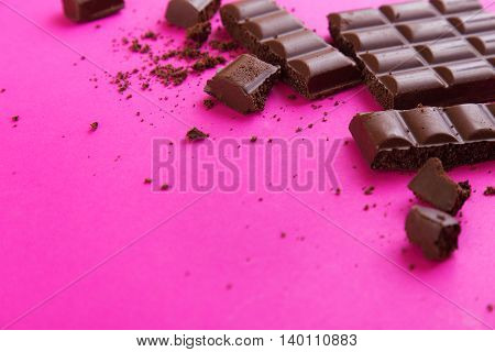 Broken dark chocolate bar with crumbs on a pink paper background