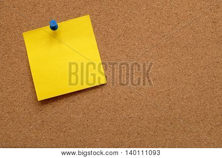 Blank yellow note paper pinned to a cork notice board with copy space