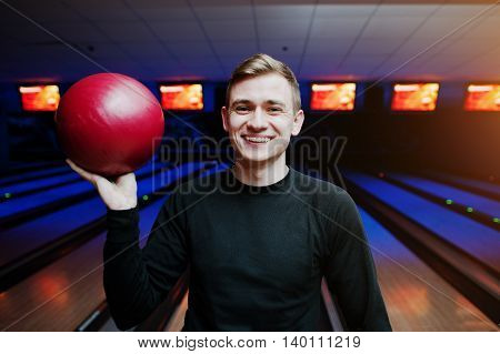 Cheerful Young Man Holding A Bowling Ball And Smiling At Camera While Standing Against Bowling Alley