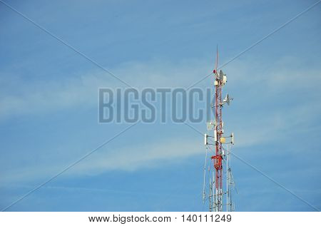 radio pole (telecommunication antenna) on blue sky and soft clouds background