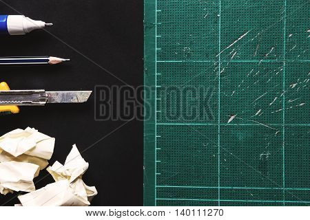 Old scratch cutting mat with cutter,pencil and liquid eraser and crumpled paper ball