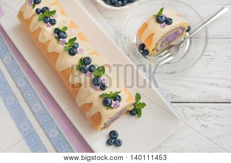 Sponge roll with with cream and blueberries on wooden background