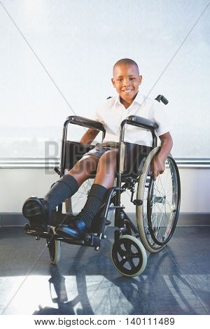 Portrait of happy schoolkid sitting on wheelchair in classroom at school