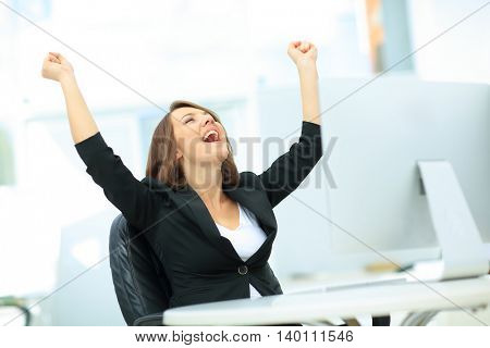 Exited, successful business woman looking up