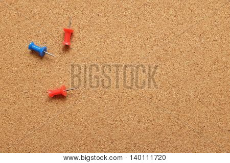 Three Push Pins On A Cork Noticeboard
